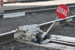 This device derails freight trains when active. Track workers activate it to isolate a section of track and lock it in place with their personal padlocks. The device will remain active until the last padlock is removed.